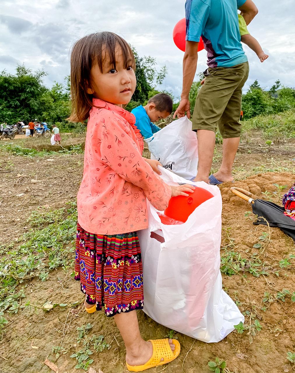 Cô bé người H'Mông nhận quà của xưởng áo thun Say Happy